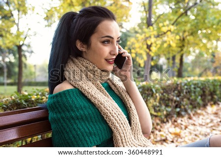 Portrait of smiling woman talking on phone while sitting on bench in park - stock photo