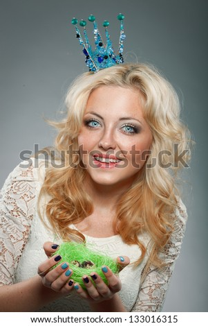 portrait of smiling woman wearing  blue princess crown and holding nest with quail eggs - stock photo