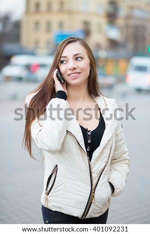 Portrait of smiling woman wearing white jacket posing with mobile phone outdoors - stock photo