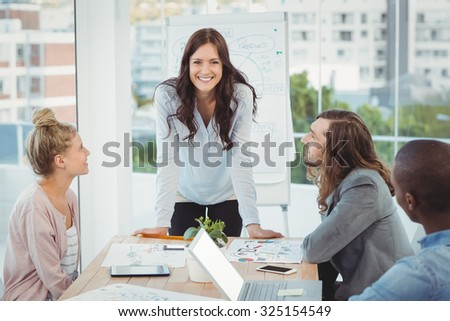 Portrait of smiling woman while coworkers looking at her in office - stock photo