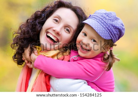 Portrait of smiling woman with cute little girl in autumn park - stock photo