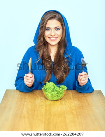 Portrait of smiling woman with diet vegetarian food. Young female model sitting at table. - stock photo