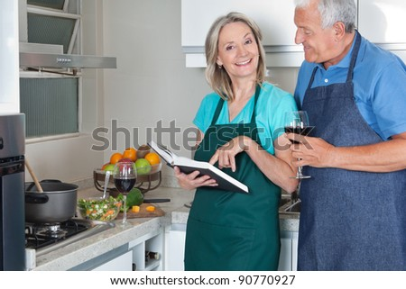 Portrait of smiling woman with recipe book and man holding wine glass in kitchen - stock photo