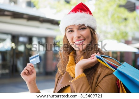 Portrait of smiling woman with santa hat and shopping bags at the shopping mall - stock photo