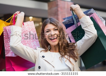 Portrait of smiling woman with shopping bags looking at camera at the shopping mall - stock photo
