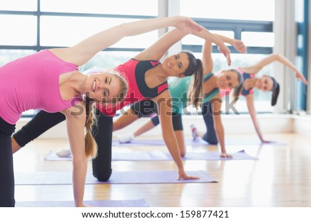 Portrait of smiling women doing the side plank yoga pose at yoga class in fitness studio - stock photo