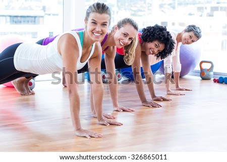 Portrait of smiling women exercising on floor in fitness studio - stock photo