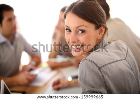 Portrait of smiling working girl in meeting - stock photo