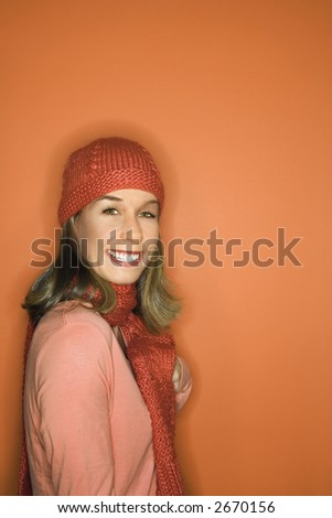 Portrait of smiling young adult Caucasian woman on orange background wearing winter hat and scarf.