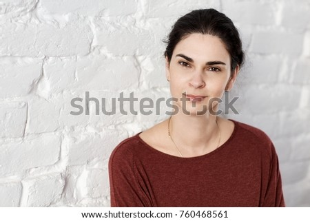 Portrait of smiling young adult woman leaning against white brick wall, looking at camera. Lifestyle portrait photo with copyspace.