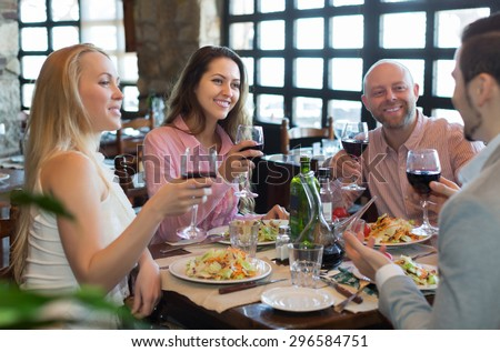 Portrait of smiling young adults having dinner in family restaurant. Focus on brunette girl - stock photo
