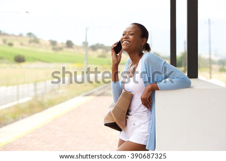 Portrait of smiling young african woman standing with cell phone and bag
