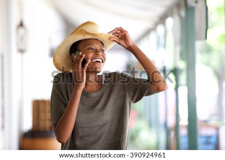 Portrait of smiling young african woman with hat talking on cell phone - stock photo