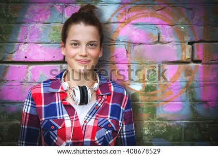 Portrait of smiling young and nice teenager girl with headphones. Low light. - stock photo