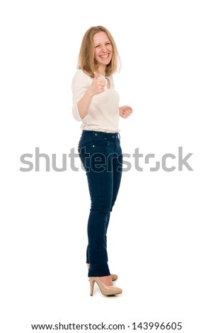 Portrait of smiling young beautiful woman in a light blouse and dark jeans at full height raises the thumb, isolated on white background.