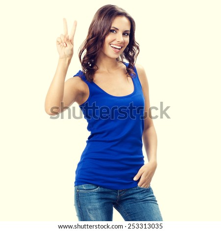 Portrait of smiling young beautiful woman showing two fingers or victory gesture - stock photo