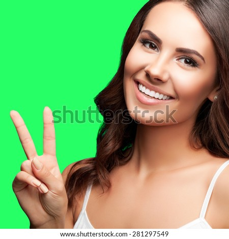 Portrait of smiling young beautiful woman showing two fingers or victory gesture, isolated over green screen chroma key background - stock photo