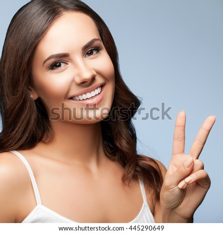 Portrait of smiling young beautiful woman showing two fingers or victory gesture, over grey background