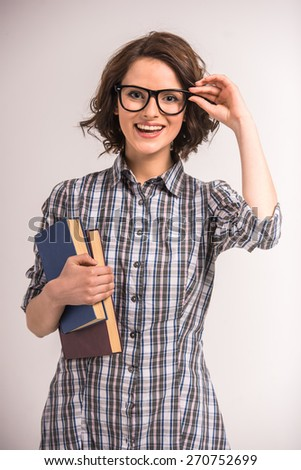 Portrait of smiling young beauty woman in glasses with books on grey background. - stock photo