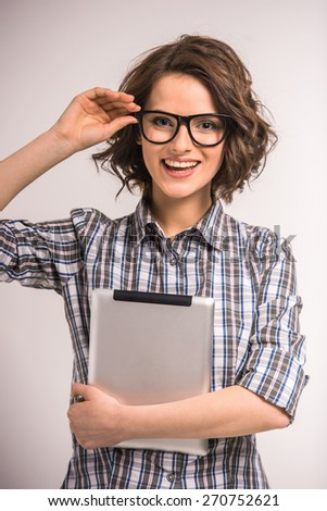 Portrait of smiling young beauty woman in glasses with tablet on grey background. - stock photo