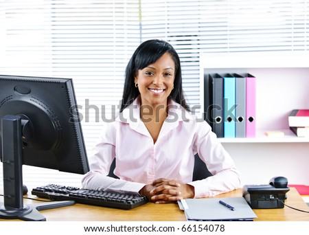 Portrait of smiling young black business woman at desk in office - stock photo
