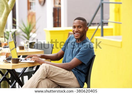 Portrait of smiling young black guy sitting at a cafe with a laptop - stock photo