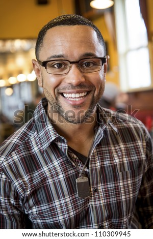 Portrait of smiling young black man in the interior of coffee shop. - stock photo