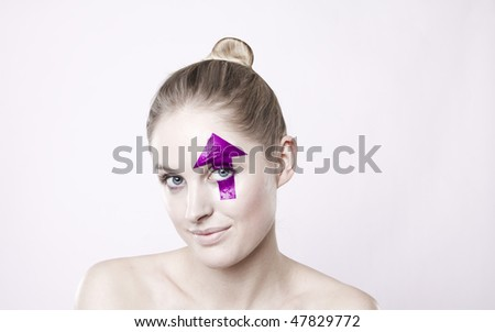 Portrait of smiling young blond haired woman with upward pointing arrow painted over eye, white studio background. - stock photo