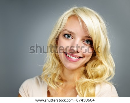 Portrait of smiling young blonde caucasian woman on grey background