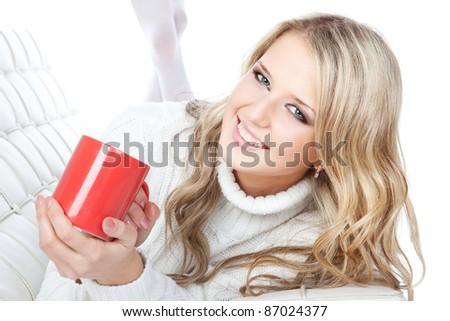 Portrait of smiling young blonde woman holding cup of coffee or tea over white - stock photo
