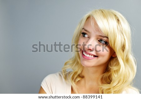 Portrait of smiling young blonde woman looking to the side on grey background - stock photo