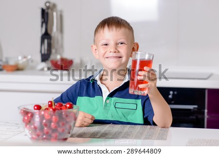 Portrait of Smiling Young Boy Drinking Glass of Red Juice While Sitting at Table with Bowl of Cherries in Kitchen