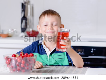 Portrait of Smiling Young Boy Drinking Glass of Red Juice While Sitting at Table with Bowl of Cherries in Kitchen with Eyes Closed