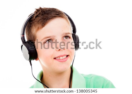 Portrait of smiling young boy listening to music on headphones against white background