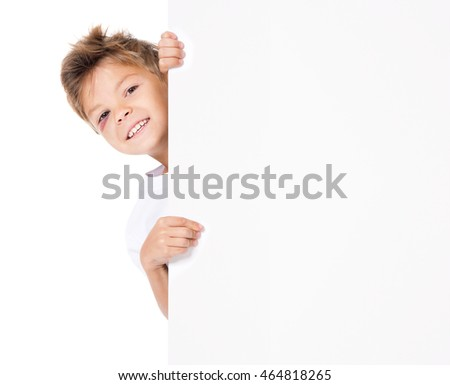 Portrait of smiling young boy with bruise, peeking through billboard, isolated on white background. Close up of happy cute kid with blank white poster. Child holding empty placard and looking at