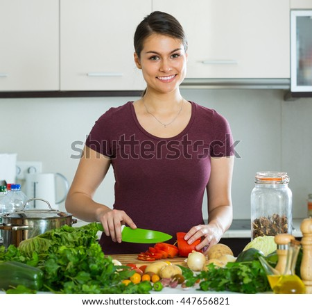 Portrait of smiling young brunette with vegetables at kitchen table
