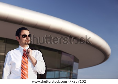 Portrait of smiling young business person in white shirt, orange tie and sunglasses standing in front of office building. - stock photo