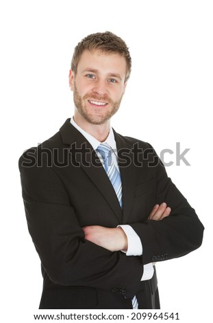 Portrait of smiling young businessman standing arms crossed over white background