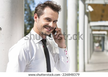 Portrait of smiling young businessman using cell phone outside office - stock photo