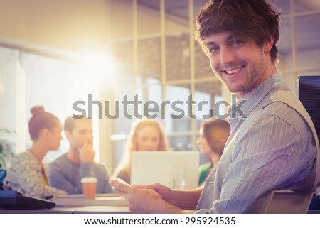 Portrait of smiling young businessman with colleagues in the office - stock photo