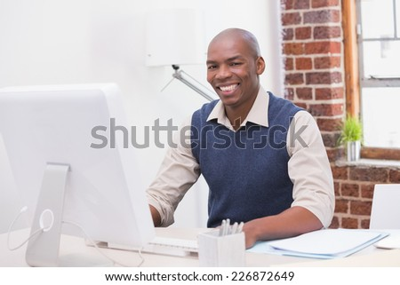 Portrait of smiling young businessman with computer at office desk