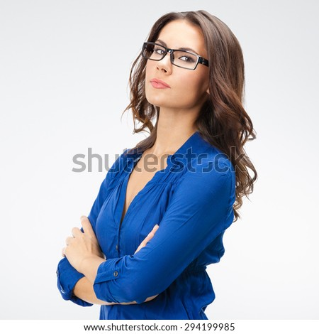 Portrait of smiling young businesswoman, in glasses, posing at studio against grey background - stock photo