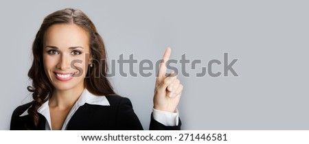 Portrait of smiling young businesswoman showing blank copyspace area for text or slogan - stock photo