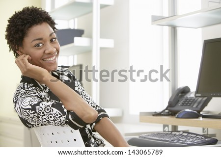 Portrait of smiling young businesswoman sitting at computer desk in office - stock photo
