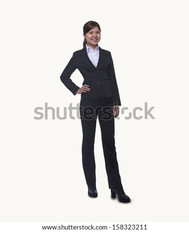 Portrait of smiling young businesswoman with hand on hip