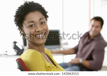 Portrait of smiling young businesswoman with male colleague in background - stock photo