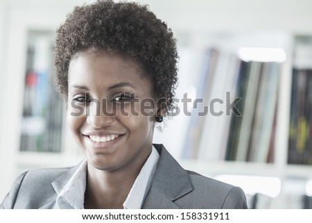Portrait of smiling young businesswoman with short hair looking at the camera - stock photo