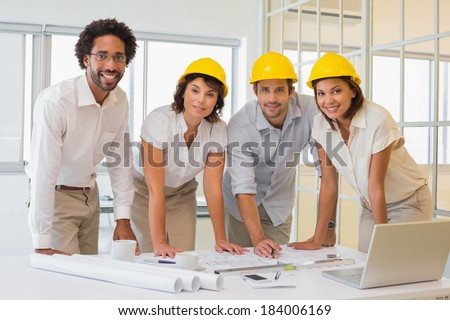 Portrait of smiling young colleagues working on blueprints at the office - stock photo