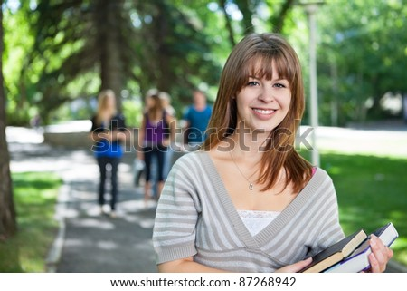 Portrait of smiling young college girl with her friends in background