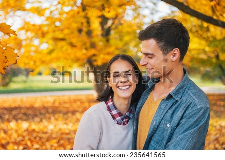 Portrait of smiling young couple outdoors in park in autumn - stock photo